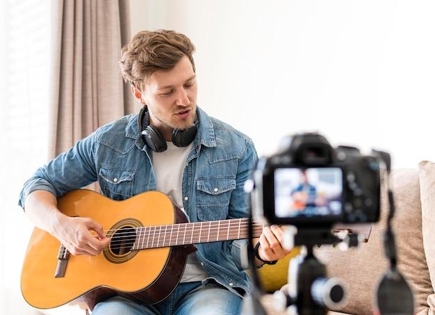 Enregistrement Masculin Beau Tout En Jouant De La Guitare Photo gratuit