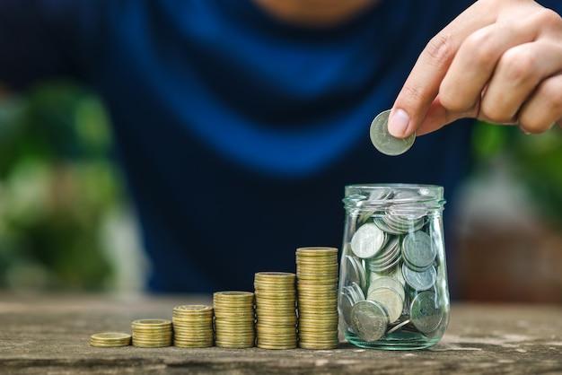 Enregistrer le concept d'argent avec la main tenant la pièce sur la pile de pièces Photo Premium