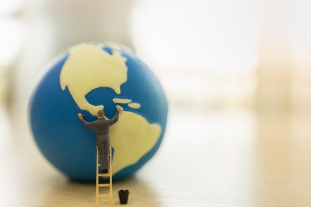 Enregistrez Le Concept De Protection De L'environnement Mondial. Grand Plan, De, Ouvrier, Miniature, Gens, Debout, Sur, Escalier, Et, Nettoyage, Mini Monde, Balle, à, Réservoir Eau, Sur, Table Bois Photo Premium