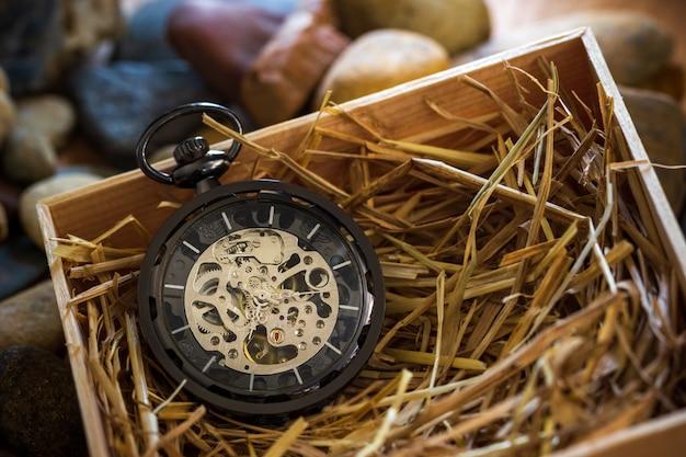 Enrouleur de montre de poche sur paille de blé naturelle dans une boîte en bois. Photo Premium