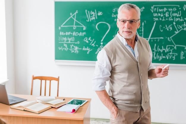 Enseignant âgé avec une craie expliquant les mathématiques Photo gratuit