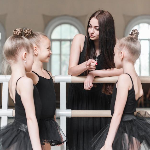 Enseignant donnant des instructions à ses filles de ballet dans un studio de danse Photo gratuit