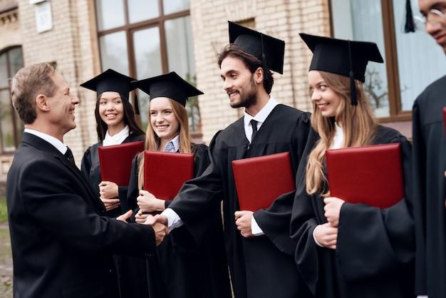 L'enseignant donne aux étudiants des diplômes dans la cour Photo Premium