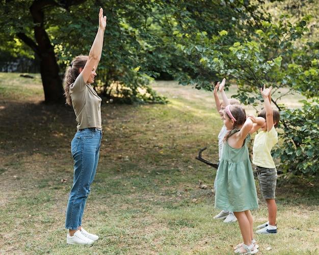 Enseignant Et Enfants Avec Les Mains En L'air Photo gratuit