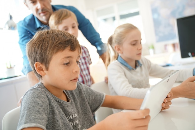 Enseignant avec des étudiants dans un cours d'informatique Photo Premium