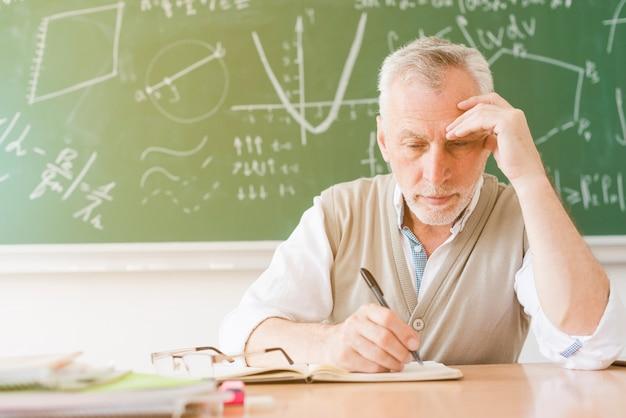 Enseignant fatigué âgé écrivant dans un cahier en classe Photo gratuit