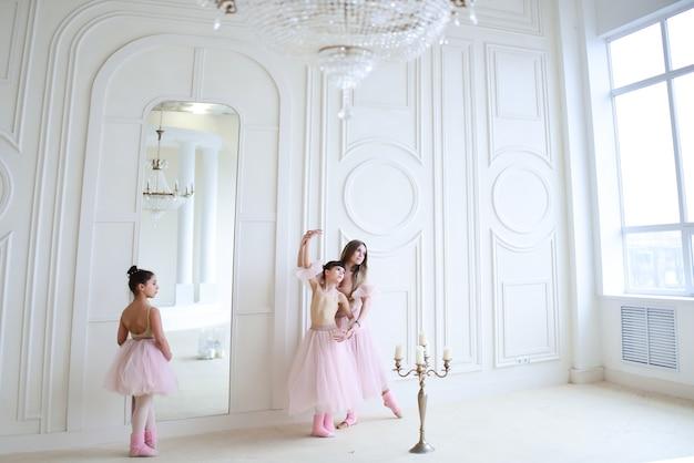 L'enseignant forme des mouvements de ballet avec des petites filles vêtues de vêtements roses dans la pièce Photo gratuit