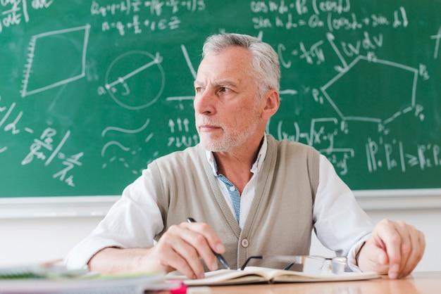 Enseignant sérieux regardant loin dans la salle de classe Photo gratuit