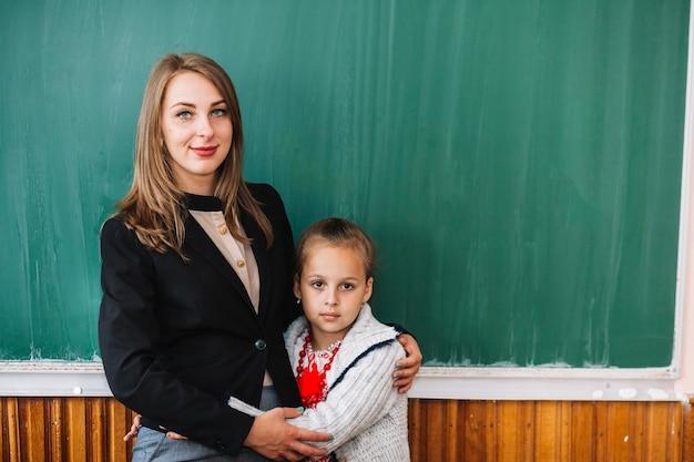 Enseignante avec une étudiante debout et câlins Photo gratuit