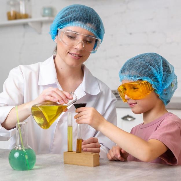 Enseignante Et Fille Avec Des Filets à Cheveux Faisant Des Expériences Scientifiques Avec Des Tubes à Essai Photo gratuit