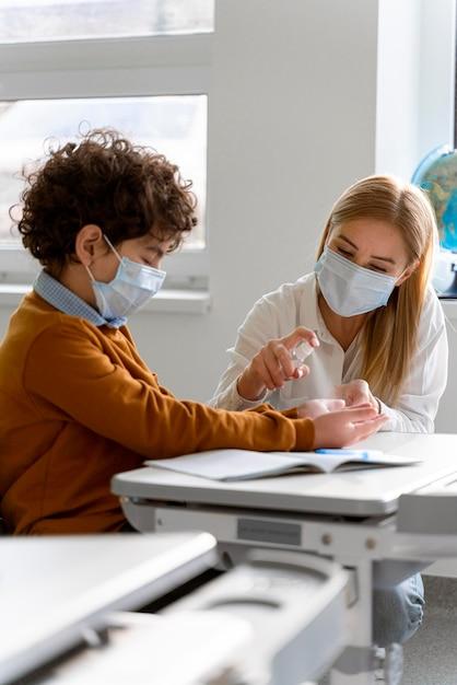 Enseignante Avec Masque Médical Désinfectant Les Mains De L'élève En Classe Photo gratuit
