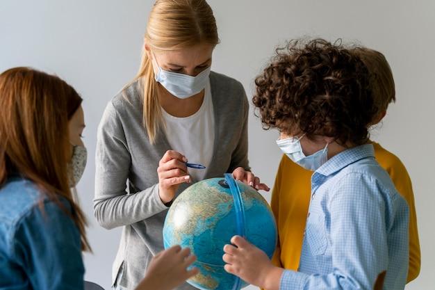 Enseignante Avec Masque Médical Enseignant La Géographie Avec Globe En Classe Photo Premium