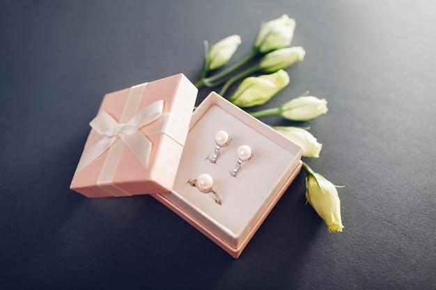 Ensemble de bijoux de perles dans une boîte cadeau avec des fleurs. boucles d'oreilles en argent et bague avec perles en cadeau Photo Premium