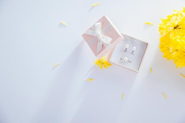 Ensemble de bijoux de perles dans la boîte-cadeau avec des fleurs Photo Premium