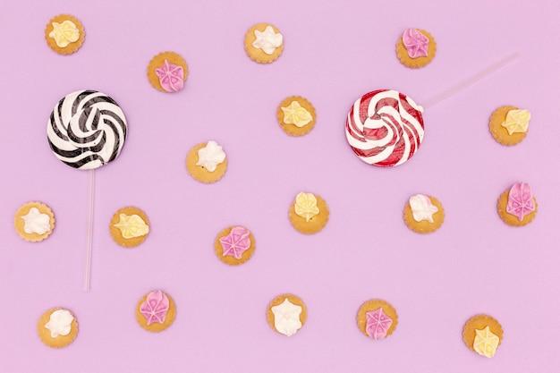 Ensemble de bonbons et sucettes sur fond violet Photo gratuit