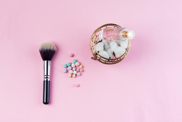 Ensemble de boules de cosmétiques colorés de coton, de parfum et de pinceau sur fond rose. Photo Premium