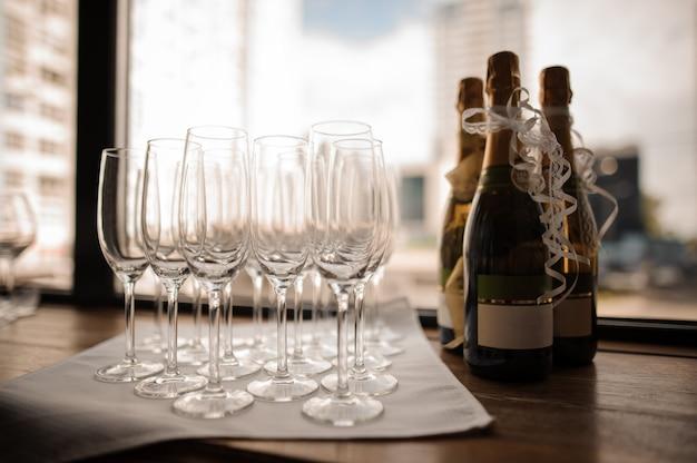 Ensemble de bouteilles de champagne et de verres à vin vides sur la serviette Photo Premium