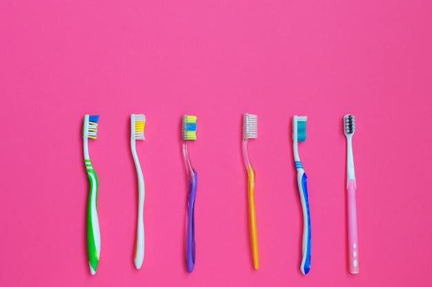Ensemble de brosses à dents différentes sur fond rose. Photo Premium