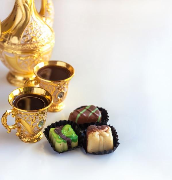 Ensemble de café arabe doré traditionnel de nature morte avec bonbons au chocolat, dallah et tasse. Photo Premium