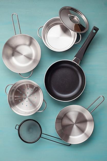 Ensemble de casseroles métalliques de cuisine. maquette, ustensiles de cuisine, livre de recettes et concept de cours de cuisine Photo Premium