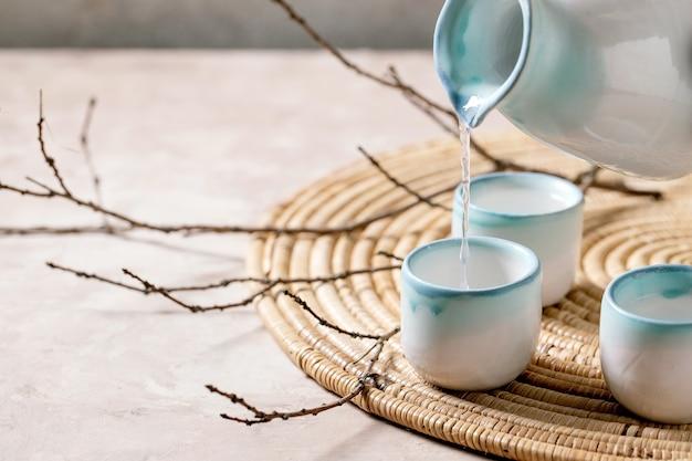 Ensemble En Céramique De Saké Pour Boisson Alcoolisée Japonaise Traditionnelle Versant Du Pichet Dans Trois Tasses Photo Premium