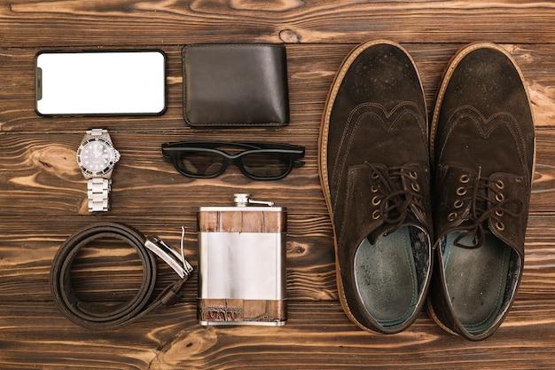 Ensemble de chaussures hommes près de smartphone et accessoires Photo gratuit