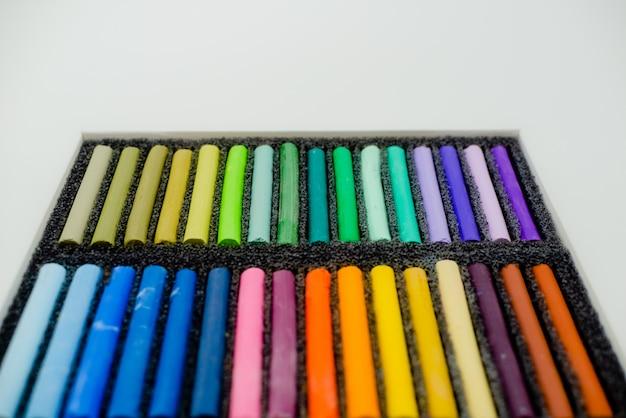 Ensemble de crayons pastels multicolores dans une boîte openartist sur fond blanc, vue de dessus. Photo Premium