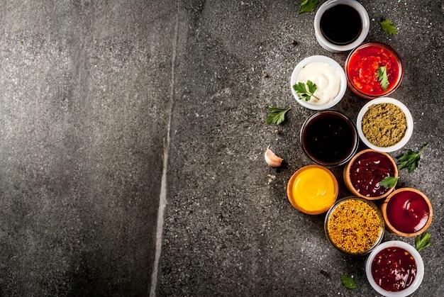 Ensemble De Différentes Sauces Ketchup, Mayonnaise, Barbecue, Soja, Teriyaki, Moutarde, Grain Hills, Pesto, Adzhika, Chutney, Tkemali, Sauce à La Grenade Sur Pierre Noire. Vue De Dessus Photo Premium