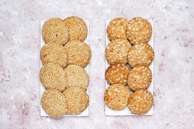 Ensemble De Divers Cookies De Style Américain Sur Un Fond De Béton Clair. Sablés Aux Confettis, Graines De Sésame, Beurre D'arachide, Biscuits à L'avoine Et Aux Pépites De Chocolat. Photo gratuit