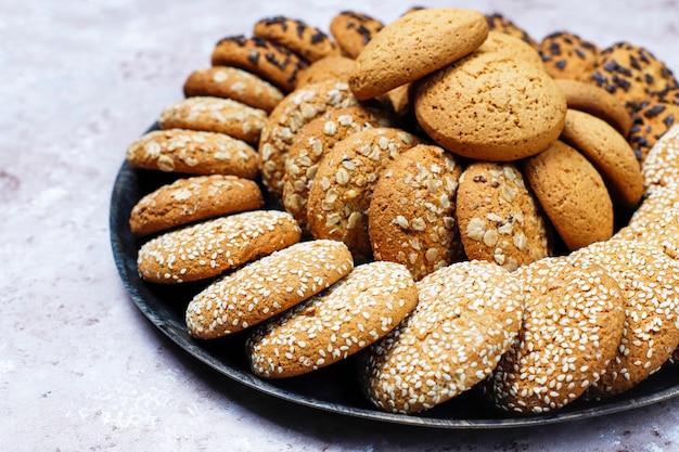 Ensemble De Divers Cookies De Style Américain Sur Un Fond De Béton Clair. Sablés Aux Confettis, Graines De Sésame, Beurre D'arachide, Biscuits à L'avoine Et Aux Pépites De Chocolat. Photo Premium
