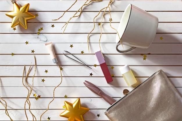 Ensemble du nouvel an de produits cosmétiques maquillage pour femmes sur fond en bois avec des étoiles dorées. Photo Premium