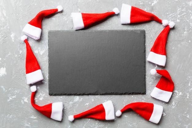 Ensemble festif d'assiette décorée avec un chapeau de père noël sur une surface en ciment Photo Premium