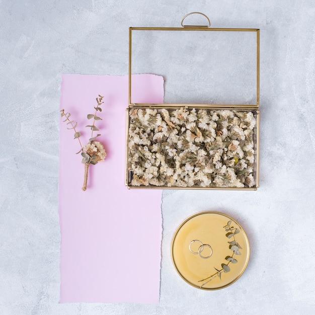 Ensemble de fleurs en boîte et papier près des anneaux sur la ronde Photo gratuit