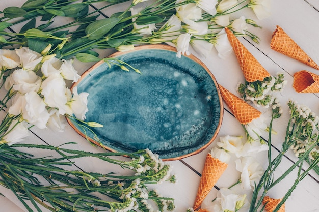 Ensemble De Fleurs Et De Cornets De Crème Glacée Et Plaque Bleue Sur Bois Blanc. Vue De Dessus. Photo gratuit