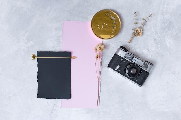 Ensemble de fleurs près de papiers, anneaux sur appareil photo rond et rétro Photo gratuit