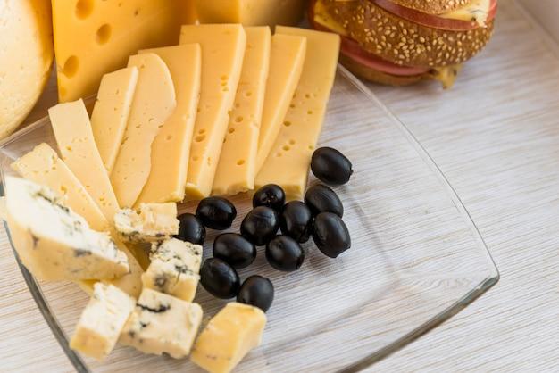 Ensemble de fromage frais et olives sur plat près de sandwich Photo gratuit