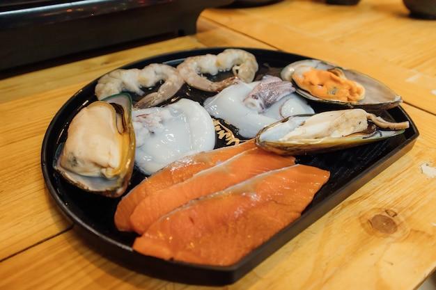 Ensemble de fruits de mer crus servis dans un style restaurant shabu. Photo Premium