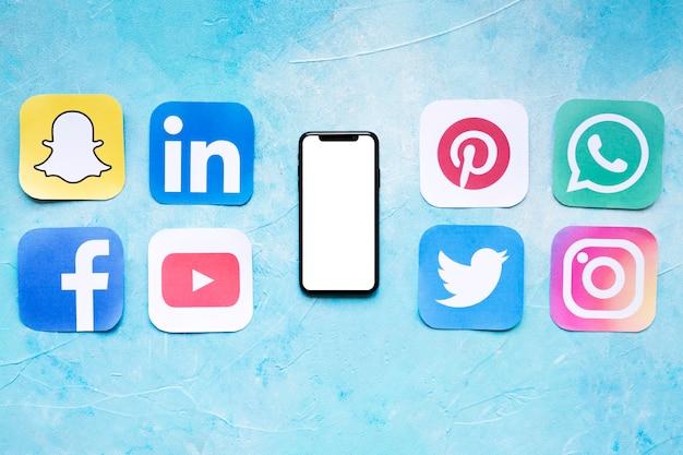 Ensemble d'icônes de réseaux sociaux placés près de smartphone Photo gratuit