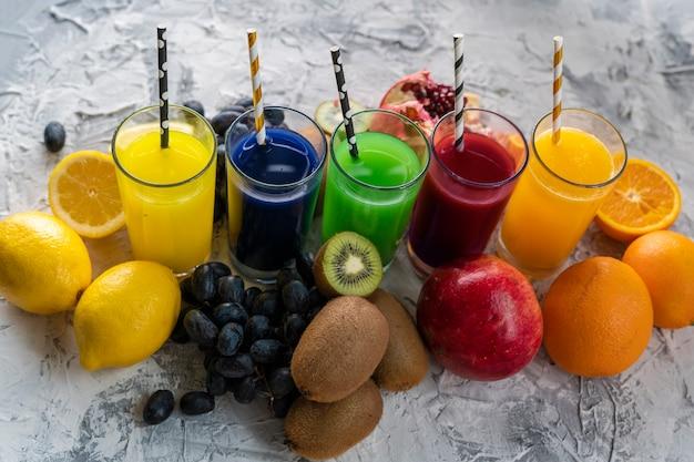Un ensemble de jus de fruits fraîchement pressés ou de cocktails dans des verres à base d'orange, kiwi, citron, raisins, grenades Photo Premium