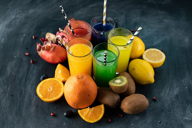 Un ensemble de jus de fruits fraîchement pressés ou de cocktails dans des verres à base d'orange, kiwi, citron, raisins, grenades Photo Premium
