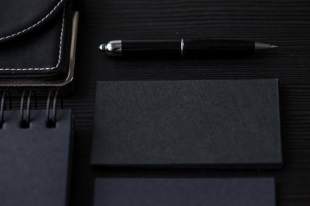 Ensemble de maquettes noires sur sombre, main féminine tenant une carte de visite Photo Premium