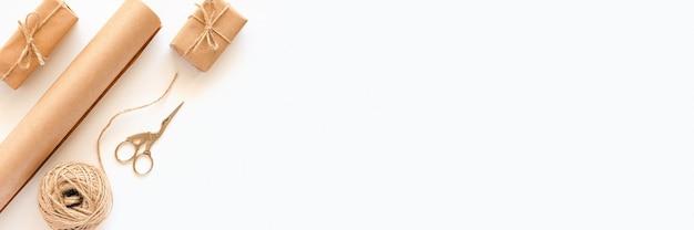 Ensemble De Matériaux Pour Emballer Les Cadeaux De Vacances. Bannière En Papier Kraft, Ficelle De Jute, Ciseaux, Boîtes Sur Fond Blanc. Photo Premium