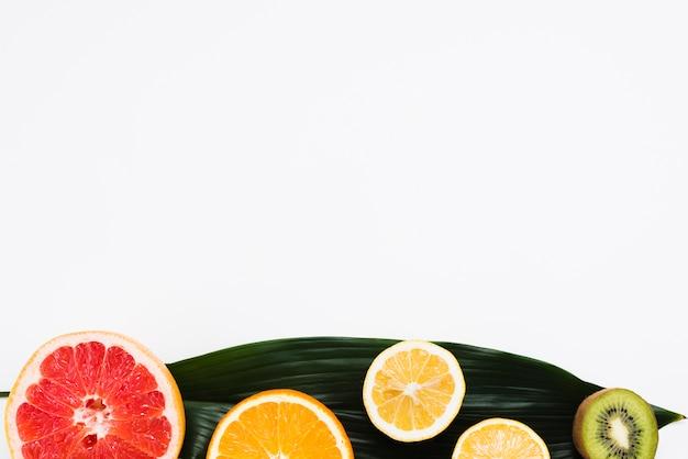 Ensemble de la moitié des fruits tropicaux sur une feuille de bananier sur fond blanc Photo gratuit