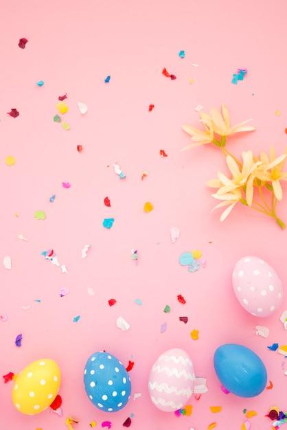 Ensemble d'oeufs de pâques entre confettis brillants Photo gratuit