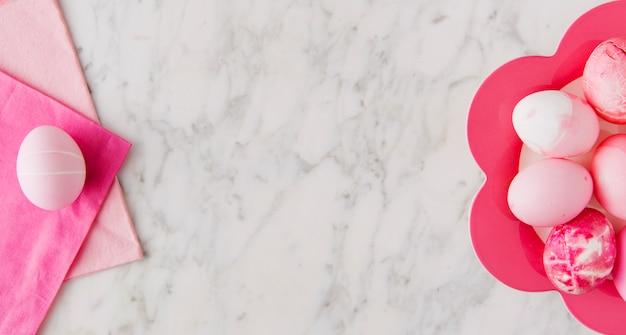 Ensemble d'oeufs de pâques roses sur assiette et serviettes Photo gratuit