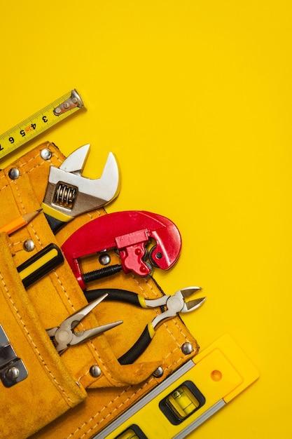 Ensemble D'outil Dans Un Sac En Daim Sur Fond Jaune Préparé Par Le Maître électricien Plombier Avant Réparation Ou Construction Photo Premium