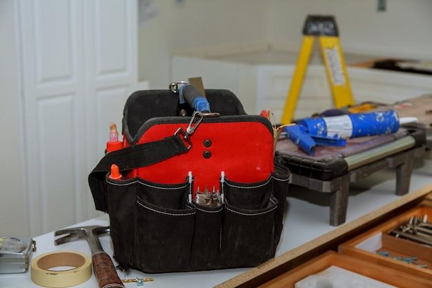 Ensemble d'outils dans un sac sur fond en bois Photo Premium