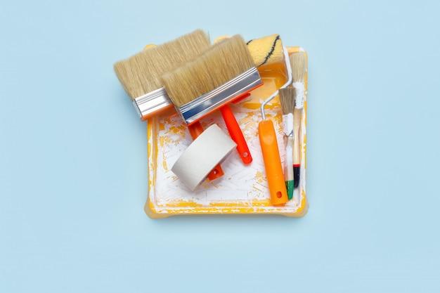 Ensemble d'outils pour la peinture: pinceaux, ruban adhésif, rouleau à peinture sur fond bleu clair. Photo Premium