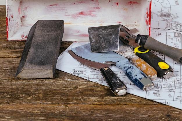 Ensemble d'outils de truelle de plâtre et de la spatule sur le vieux bois de fond. Photo Premium
