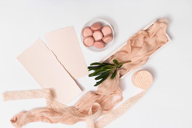 Ensemble de papier et macarons sur une assiette près de textile Photo gratuit
